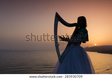 Silhouette woman plays harp by the sea at sunset in Santorini, Greece - stock photo