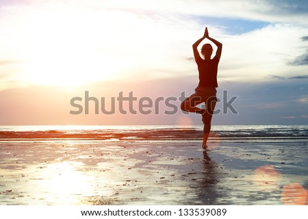 Silhouette woman practicing yoga on the beach at sunset - stock photo