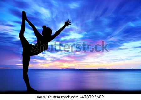 Silhouette woman with yoga posture on the beach at sunset.