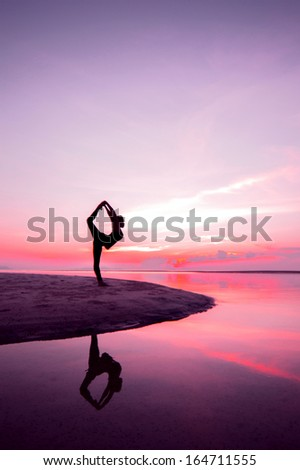 Silhouette woman with yoga posture on the beach at sunset with reflection. - stock photo