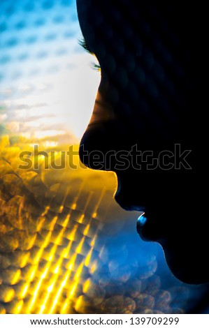 silhouette women face on color sunlight background - stock photo