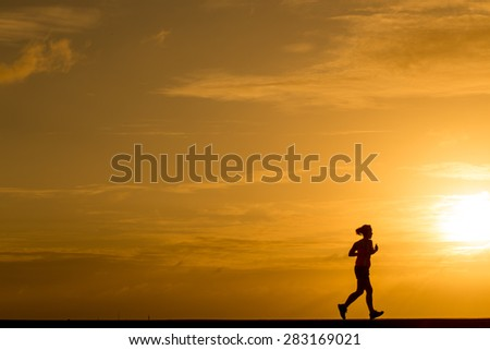Silhouette women jogging at sunset - stock photo