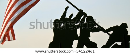 Silhouette wood cutout of American servicemen raising the American Flag. A real United States flag blows in the wind. Warm morning sunlight background. - stock photo