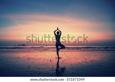 Silhouette yoga meditation girl on the background of the sea and sunset. Healthy lifestyle. - stock photo