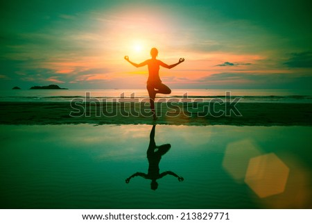 Silhouette yoga woman on sea coast at surreal sunset (abstract photo about healthy lifestyle) - stock photo