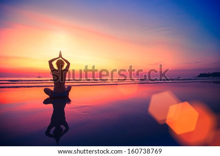 Silhouette yoga woman sitting on sea coast at beautiful sunset. - stock photo