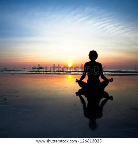 Silhouette yoga woman sitting on sea coast at sunset. - stock photo