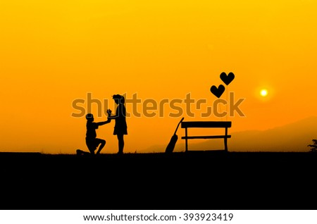 Silhouette Young boy giving flowers to loved ones. sunset - stock photo