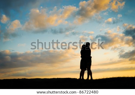 Silhouette young couple  at sunset - stock photo