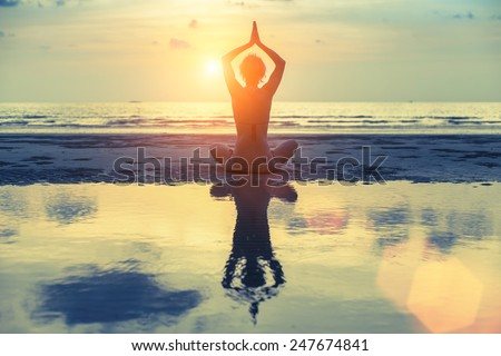 Silhouette young female practicing yoga on the beach at amazing sunset. - stock photo