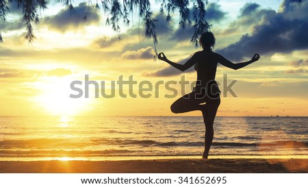 Silhouette young female practicing yoga on the beach at magnificent sunset. - stock photo