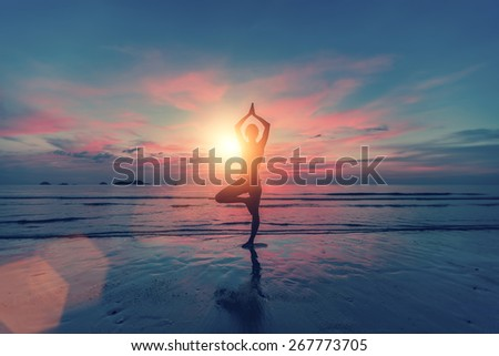 Silhouette young female practicing yoga on the beach at sunset
