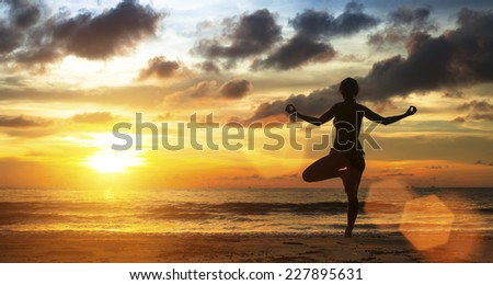 Silhouette young female practicing yoga on the sea beach at sunset. - stock photo