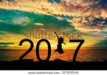Silhouette young woman jumping on the sea and 2017 years while celebrating new year - stock photo