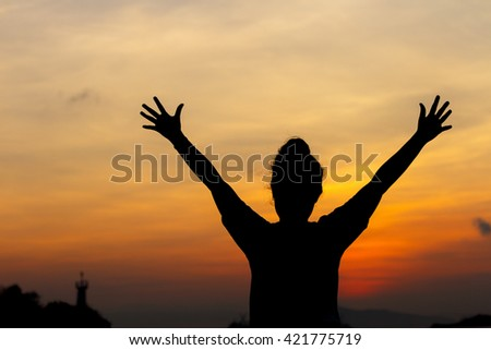 silhouette young woman lift both hands and beautiful sky at sunset background