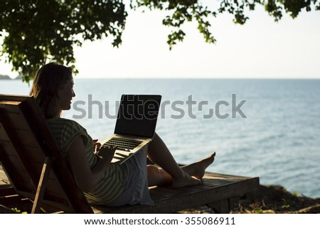 Silhouette young woman on a sun lounger with a laptop at the seaside. - stock photo