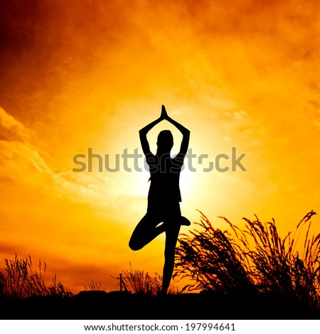 Silhouette young woman practicing yoga at  yellow, orange sunset - stock photo