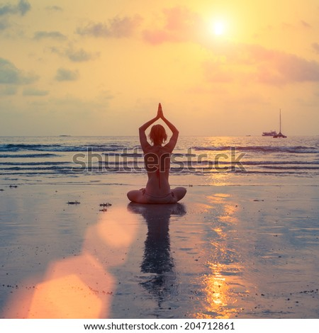 Silhouette young woman practicing yoga on beach at sunset.