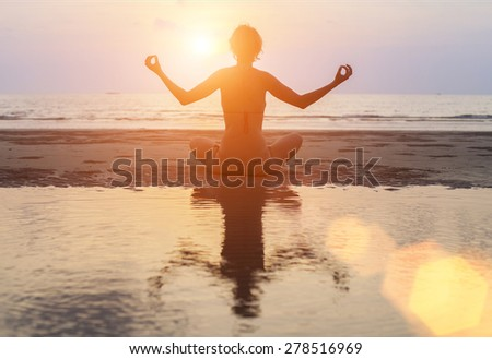 Silhouette young woman practicing yoga on Ocean beach at surrealistic sunset. - stock photo