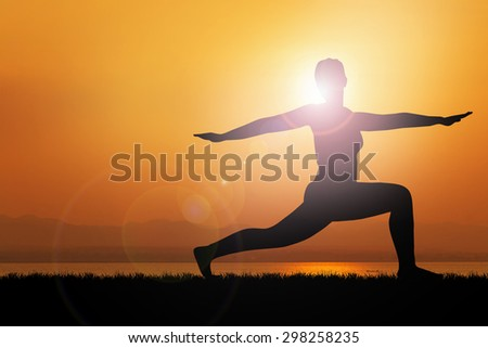 Silhouette young woman practicing yoga on sunrise