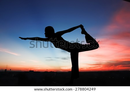 Silhouette young woman practicing yoga on sunrise in morning on town view