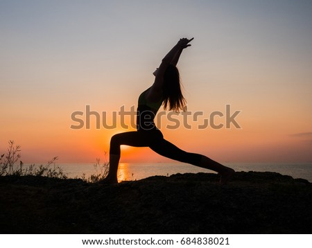 Silhouette young woman practicing yoga on the beach above sea at amazing sunset. fitness, sport, yoga and healthy lifestyle concept.