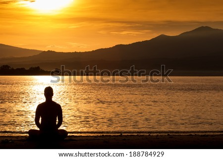 Silhouette young woman practicing yoga on the beach at sunrise on the background of mountains