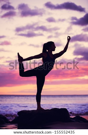 Silhouette young woman practicing yoga on the beach at sunset - stock photo