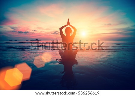 Silhouette young woman practicing yoga on the beach at sunset. Meditation.