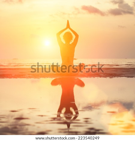 Silhouette young woman practicing yoga on the beach at surrealistic sunrise. - stock photo