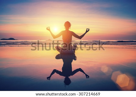 Silhouette young woman practicing yoga on the beach at surrealistic sunset. With the reflection in the wet sand.  - stock photo