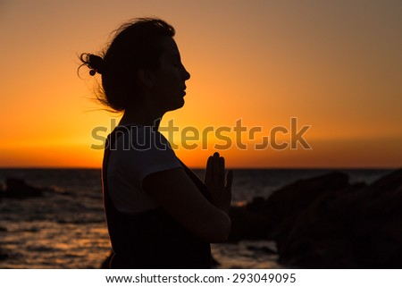 Silhouette young woman practicing yoga on the mediterranean beach at sunset.