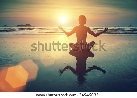 Silhouette young woman practicing yoga on the sea beach at amazing sunset. - stock photo