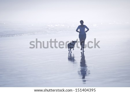 Silhouette young woman running with her dog on the beach. - stock photo
