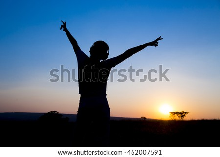 Silhouette young woman with headphone on sunrise background.
