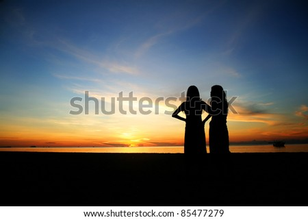 Silhouette young women looking sunset on the beach