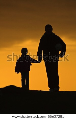Silhouetted adult and child