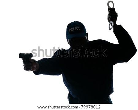 Silhouetted Afro American policeman aiming handgun while holding handcuffs isolated on white background - stock photo