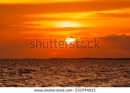 silhouetted against a colorful orange sky. - stock photo