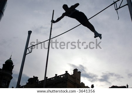 Silhouetted athlete clearing the bar during a pole vault event - stock photo