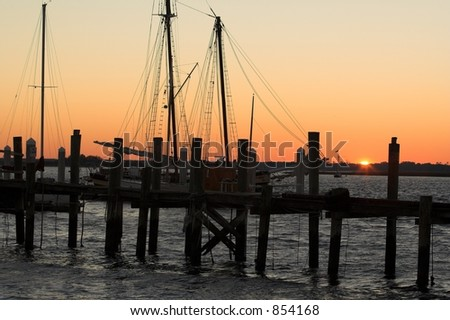 Silhouetted boats at pier, during a beautiful sunset. - stock photo