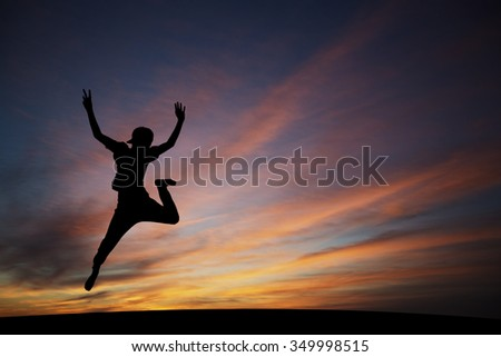 silhouetted boy jumping in sunset for fun - stock photo