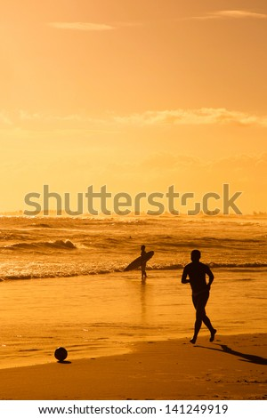 Silhouetted boy playing soccer on beach at sunset with surf boarder in background, Arraial do Cabo, Rio de Janeiro, Brazil. - stock photo