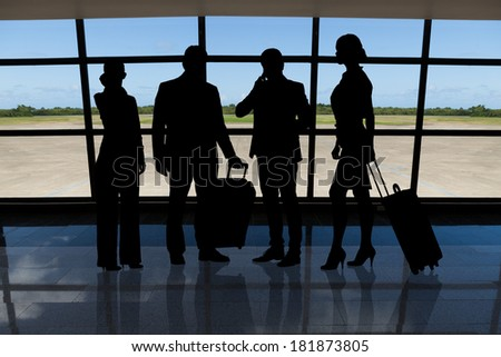 Silhouetted businesspeople with luggage standing against airport window - stock photo