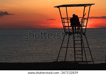 Silhouetted Couple watching the sunset from a lifeguard tower on the beach in Grand Bend Ontario. - stock photo