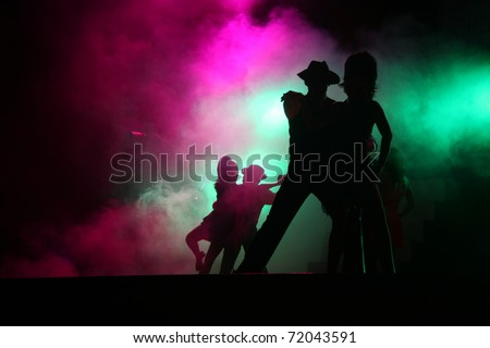 Silhouetted couples performing for theater on stage