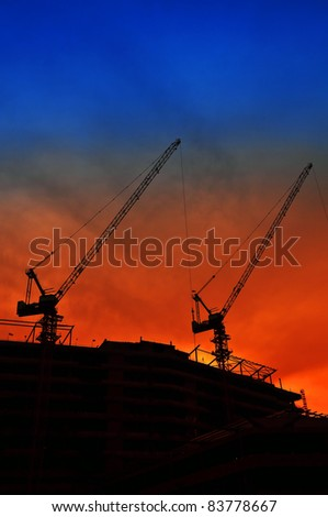 Silhouetted crane is being operated during the sunset