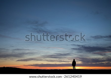 silhouetted elderly man standing in front of a sunset sky - stock photo