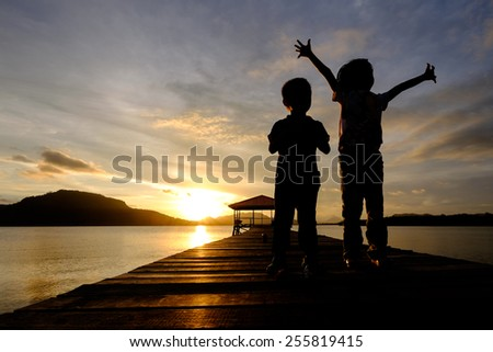 Silhouetted excited kids (Happy and joyous girl  spreads her arms and uninterested boy who does not care what his sister is doing) during sunrise - stock photo