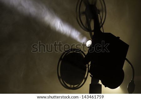 Silhouetted film projector in smokey room. - stock photo